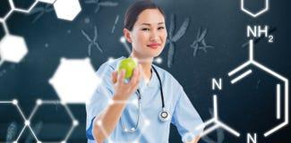 Составное изображение усмехаясь хирурга держа яблоко с коллегой в больнице Стоковые Изображения