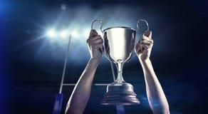 Составное изображение успешного игрока рэгби держа трофей Стоковое Изображение RF
