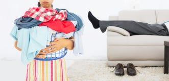 Составное изображение утомленной женщины держа полную корзину прачечной Стоковые Изображения RF