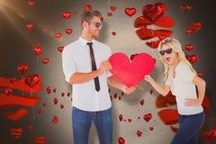 Составное изображение холодных молодых пар держа красное сердце Стоковое фото RF