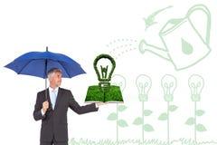 Составное изображение человека держа зонтик и лужайка записывают Стоковое фото RF
