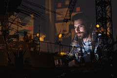 Составное изображение человека используя компьтер-книжку против места строительной конструкции Стоковое Изображение