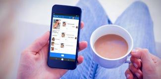 Составное изображение 3d женщины используя ее мобильный телефон и держащ чашку кофе Стоковые Изображения