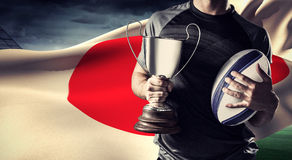 Составное изображение midsection успешного игрока рэгби держа трофей и шарик Стоковые Фотографии RF