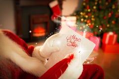 Составное изображение santa проверяя его список Стоковые Изображения RF