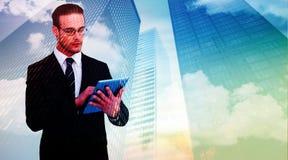 Составное изображение unsmiling бизнесмена используя ПК таблетки Стоковые Фотографии RF