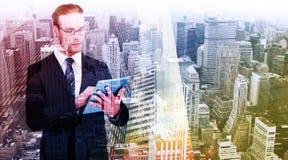 Составное изображение unsmiling бизнесмена используя ПК таблетки Стоковое Изображение