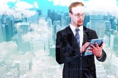 Составное изображение unsmiling бизнесмена используя ПК таблетки Стоковая Фотография