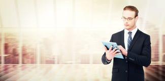 Составное изображение unsmiling бизнесмена используя ПК таблетки Стоковые Изображения