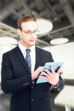 Составное изображение unsmiling бизнесмена используя ПК таблетки Стоковое фото RF