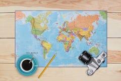 Составьте карту, старые камера, чашка кофе и карандаш кладя на деревянный стол Необходимое оборудование взгляд сверху путешествен стоковая фотография