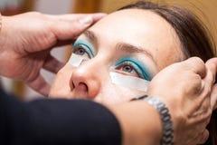 Составьте художника используя ленту для маскировки для того чтобы создать глаза кота Стоковое фото RF