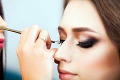 Составьте художника прикладывая тень глаза к женщине стоковая фотография rf