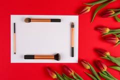 Составьте щетки аранжированные на белых тюльпанах цветков чистого листа бумаги и весны на красной предпосылке Взгляд сверху Стоковые Фото