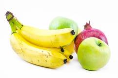 Состав бананов, зеленых яблок и гранатового дерева на белой предпосылке Стоковые Фото
