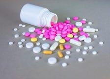 Состав бутылки и пилюлек медицины на серой предпосылке Стоковые Фото