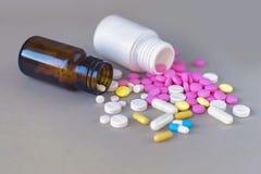 Состав бутылок и пилюлек медицины на серой предпосылке Стоковые Изображения