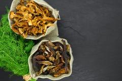 Состав взгляда сверху сухих грибов подосиновика и лисичек установил в холсте с веником укропа и петрушки на черном камне стоковое фото