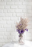Состав высушенных цветков на белом кирпиче стены в предпосылке Стоковое Изображение RF