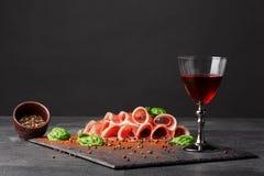 Состав гастрономии Полная рюмка, солёное jamon и зеленый шпинат на черной предпосылке Холодные алкогольные напитки Стоковое Изображение