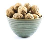 Состав грецких орехов в зеленой чашке на белой предпосылке Стоковые Изображения