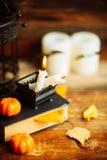 Состав декоративных черепа, тыквы, свечей и украшений хеллоуина на деревянном столе, на предпосылке темного цвета Стоковое Изображение