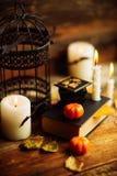 Состав декоративных черепа, тыквы, свечей и украшений хеллоуина на деревянном столе, на предпосылке темного цвета Стоковые Фото
