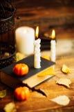 Состав декоративных черепа, тыквы, свечей и украшений хеллоуина на деревянном столе, на предпосылке темного цвета Стоковая Фотография RF