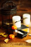 Состав декоративных черепа, тыквы, свечей и украшений хеллоуина на деревянном столе, на предпосылке темного цвета Стоковые Фотографии RF