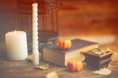 Состав декоративных черепа, тыквы, свечей и украшений хеллоуина на деревянном столе, на предпосылке темного цвета Стоковое Изображение RF
