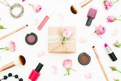Состав дня женщины с подарочной коробкой, бутонами роз, косметиками и щетками на белой предпосылке Взгляд сверху Плоское положени Стоковые Фотографии RF