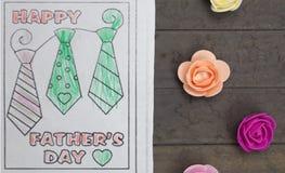 Состав дня отцов - чертеж ` s ребенка и пестротканые поддельные розы Студия снятая на деревянной предпосылке Стоковые Изображения RF