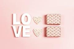 Состав дня Святого Валентина St с любовью слова, подарками и декоративными сердцами на розовой предпосылке стоковые фото