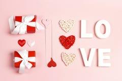 Состав дня Святого Валентина St с любовью слова, подарками и декоративными сердцами на розовой предпосылке стоковые изображения