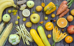 Состав желтых овощей и плодоовощей - банана, мозоли, лимона, сливы, абрикоса, перца, цукини, томата, фасолей спаржи, ginge Стоковая Фотография
