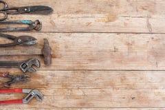 Состав инструментов конструкции на старой поколоченной деревянной поверхности инструментов: плоскогубцы, ключ для труб, отвертка, Стоковое Изображение RF
