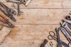 Состав инструментов конструкции на старой поколоченной деревянной поверхности инструментов: плоскогубцы, ключ для труб, отвертка, Стоковые Изображения