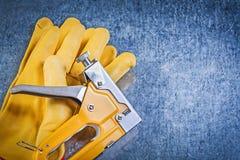 Состав кожаных перчаток безопасности скрепляет оружие на металлической задней части Стоковое Изображение
