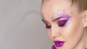 Состав красотки Фиолетовый состав и красочные яркие ногти красивейший портрет близкой девушки вверх сток-видео