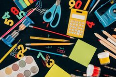 Состав красочных школьных принадлежностей изолированных на темной предпосылке доски Стоковые Изображения RF