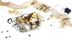 Состав натюрморта Нового Года праздничный с маской масленицы, звездами confetti черноты и золота, лентами и бокалом партия стоковые изображения