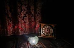 Состав дня валентинки при помадка горя пестротканое сердце на темной предпосылке и старых винтажных часах, времени и концепции вл Стоковая Фотография RF