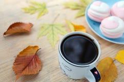 Состав осени с кофе, зефиром, желтым цветом выходит на деревянную предпосылку стоковые изображения rf