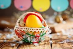 Состав пасхи яичек пасхи красочных в корзине и с гирляндой зайчика на деревянной предпосылке Стоковая Фотография RF
