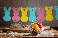 Состав пасхи яичек пасхи красочных в корзине и с гирляндой зайчика на деревянной предпосылке Стоковое Фото