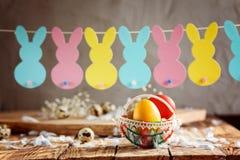 Состав пасхи яичек пасхи красочных в корзине и с гирляндой зайчика на деревянной предпосылке Стоковая Фотография