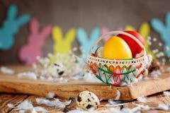 Состав пасхи яичек пасхи красочных в корзине и с гирляндой зайчика на деревянной предпосылке Стоковые Изображения