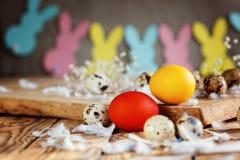 Состав пасхи яичек пасхи красочных в корзине и с гирляндой зайчика на деревянной предпосылке Стоковое фото RF