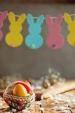 Состав пасхи яичек пасхи красочных в корзине и с гирляндой зайчика на деревянной предпосылке Стоковые Фото