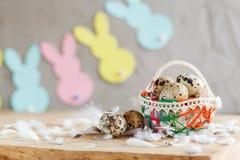 Состав пасхи яичек триперсток пасхи в корзине и с гирляндой зайчика на деревянной предпосылке Стоковое фото RF